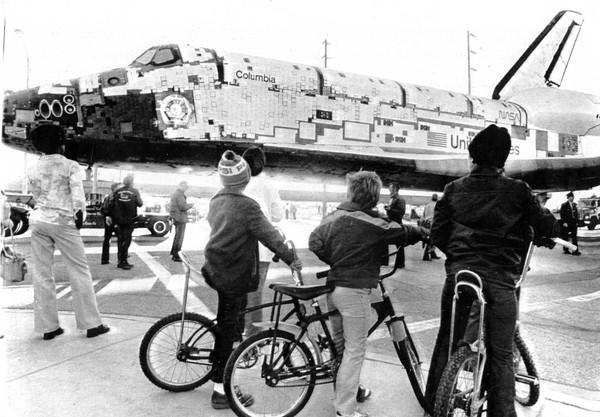 "Three boys sit on their bikes as they watch the Space Shuttle Columbia roll by the intersection of 10th and J Streets in Lancaster, Calif, on March 8, 1979. The spacecraft was being taken to Edwards Air Force Base, where it was placed atop a <a class=""taxInlineTagLink"" id=""ORCRP017215"" title=""Boeing Co."" href=""/topic/economy-business-finance/manufacturing-engineering/aerospace-manufacturing/boeing-co.-ORCRP017215.topic"">Boeing</a> 747 and flown to <a class=""taxInlineTagLink"" id=""PLCUL000170"" title=""Kennedy Space Center"" href=""/topic/science-technology/space-programs/kennedy-space-center-PLCUL000170.topic"">Kennedy Space Center</a>."