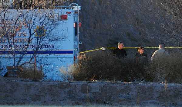 Bernalillo County sheriff's deputies investigate the scene of a multiple homicide in Albuquerque over the weekend. A 15-year-old boy confessed to shooting his parents and three young siblings, authorities said.