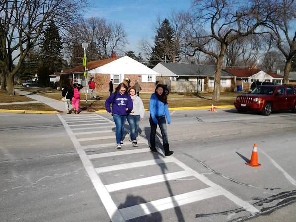 Students cross at the new flashing light near Algonquin Road and Fifth Avenue.
