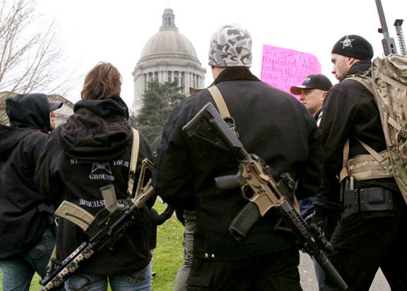 Members of Tactical Supply of Yakima carry firearms to a Second Amendment gun rally in Olympia, Wash., Saturday, Jan. 19.