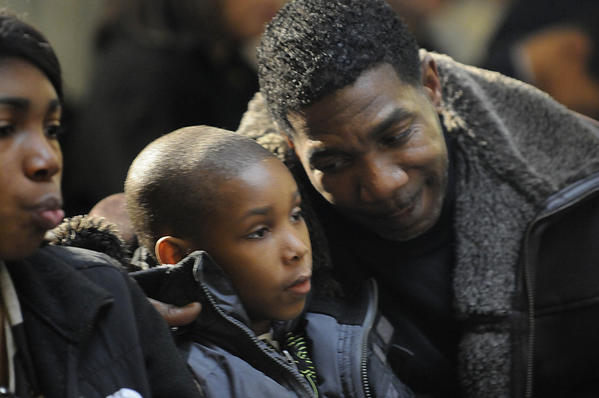 Jordan Welch, of West Haven, glances at his nephew, Jacob Welch, 7, also of West Haven, as they listen to speakers at Connecticut's 27th annual Martin Luther King, Jr. Holiday Celebration at the state Capitol Monday morning.