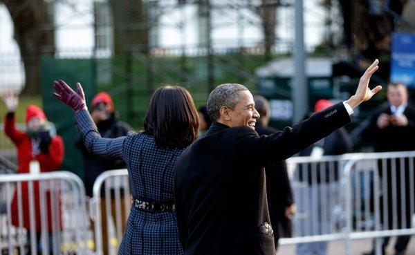 The president and first lady wave to people lining the inaugural parade route Monday in Washington.
