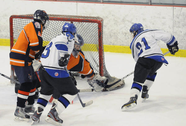 Lyman Hall East Catholic's Alex Manner (21) scores the game-winning goal in overtime against Lyman Hall's goalie Jason Culmone at Champions Skating Center Monday afternoon. East Catholic won, 4-3 and are 9-0 on the season.
