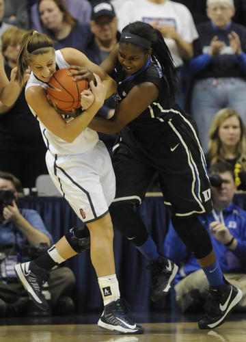 University of Connecticut Huskies guard Caroline Doty, left, and Duke Blue Devils center Elizabeth Williams battle for a rebound during the first half.