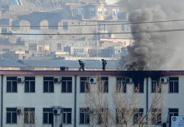 Security officers run along a rooftop at the traffic police headquarters in Kabul during a clash between Afghan forces and militants.