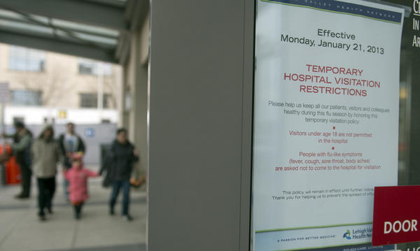 A sign outside main entrance of Lehigh Valley Hospital-Cedar Crest announces restrictions to visitors under 18 and those showing signs of illness.