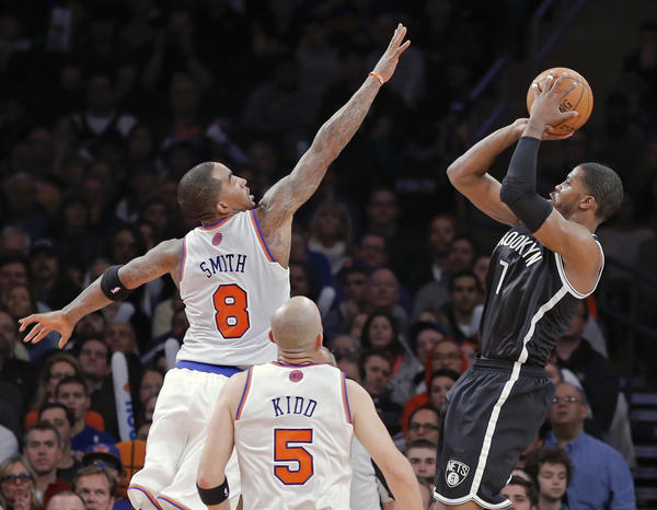 Brooklyn Nets' Johnson shoots three-point shot over New York Knicks' Smith and Kidd in NBA game in New York.