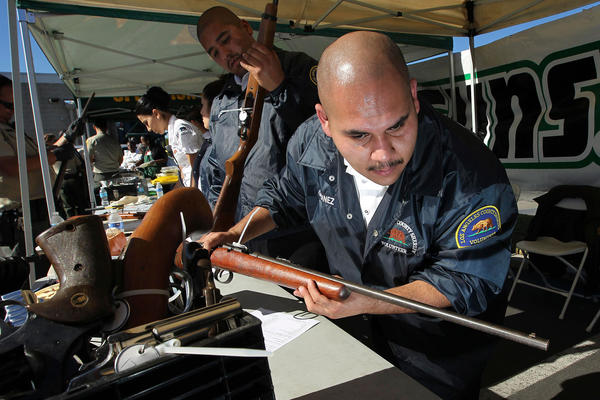 "A Los Angeles County Sheriff's volunteer catalogues guns being traded in at the ""Gifts for Guns"" gun buyback in Compton, California, January 21, 2013. People can trade in their guns anonymously and with no questions asked in exchange for $200 gift cards for assault weapons, $100 gift cards for shotguns, handguns and rifles, and $50 for non-operational firearms. U.S. President Barack Obama is pushing to address controversial issues surrounding gun violence and regulation as he begins his second term in office."