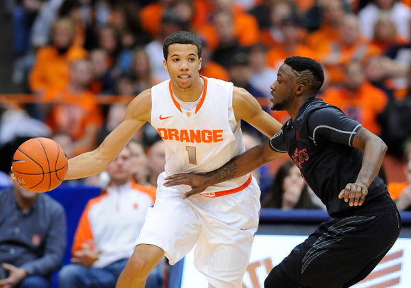 Syracuse Orange guard Michael Carter-Williams (1) makes a pass around Cincinnati Bearcats guard Cashmere Wright (1) during the first half at the Carrier Dome.