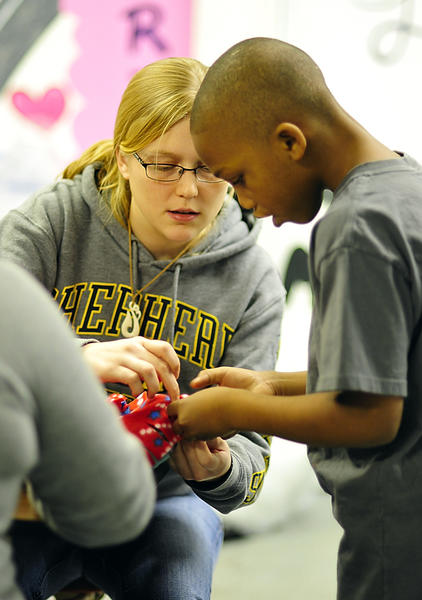 Shepherd University senior Kyra Wood assists Khalil McCoy, 9, in knotting fleece pillow covers Monday at the Boys & Girls Club in Martinsburg.