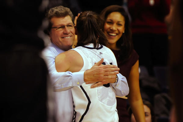 UConn coach Geno Auriemma hugs guard Kelly Faris after the game as assistant coach Marisa Moseley looks on. Faris had 18 points, 12 rebounds and six assists.