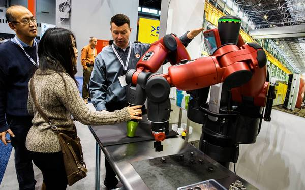 Rethink Robotics' Matt Fitzgerald, center, demonstrates Baxter, a robot that is meant to learn different tasks and work next to humans.