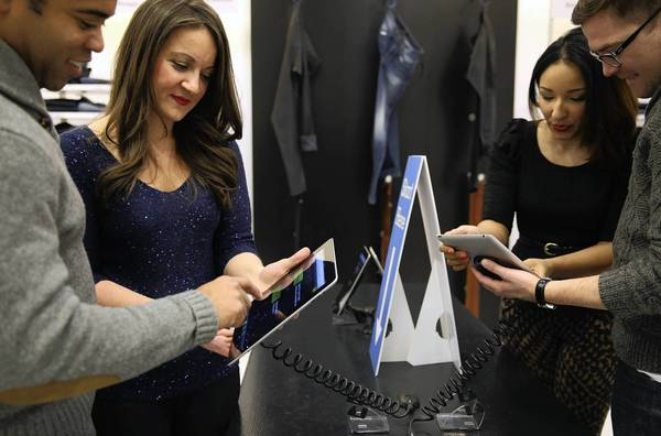 Liz Kammel, second from left, co-founder and CEO of ZipFit Denim, and Alex Batdorf, chief marketing officer, demonstrate for Joseph Adams, left, and Bradley Trovillion how to find the right jeans size for their body type by using an algorithm app on an iPad.