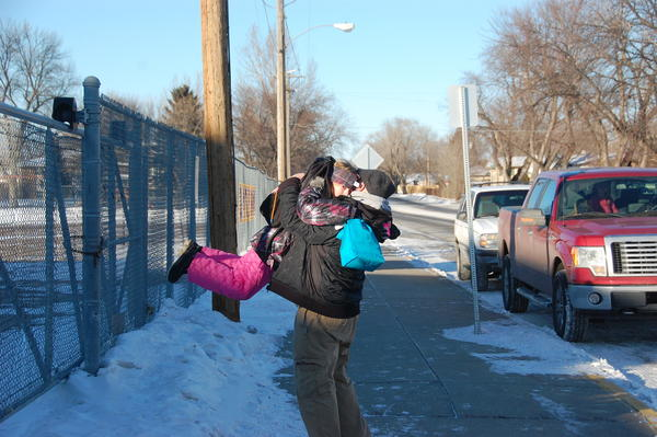Scott Swenson lifts his niece Emily Jaragoske, a second-grader at O.M. Tiffany Elementary, up into the air while he picks up her from school.