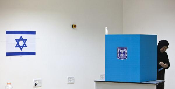 An Israeli Arab woman stands behind a booth as she casts her ballot for the parliamentary election at a polling station in the town of Tira January 22, 2013. Israelis voted on Tuesday in an election that is expected to see Prime Minister Benjamin Netanyahu win a third term in office, pushing the Jewish state further to the right, away from peace with the Palestinians and towards a showdown with Iran.