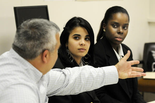 Robert Reader, school program manager at the Hartford Stage. talks to Bulkeley High School seniors Inelyz Martinez, center, and Danessa Pedroso, right, about organizing a Unified Theater Program.