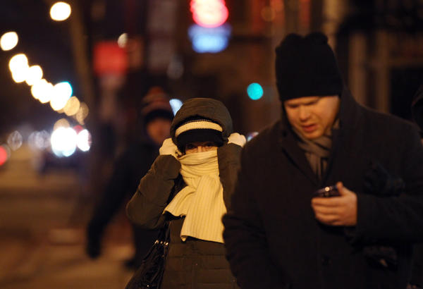 A woman adjusts her scarf and hat while walking on North Damen Avenue in the Wicker Park neighborhood.