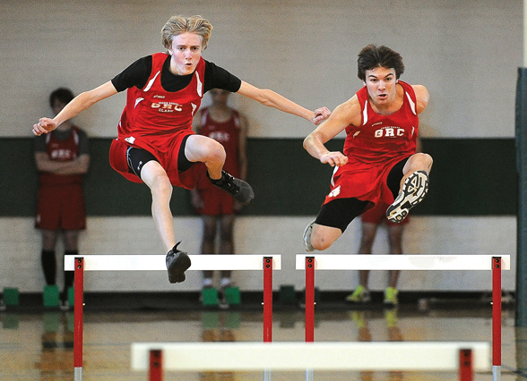 George Rogers Clark High School runners Jesse Camp, left, and Deven Gonzalez, right, competed in a hurdles event during an indoor track and field meet Monday at College Park Gym.