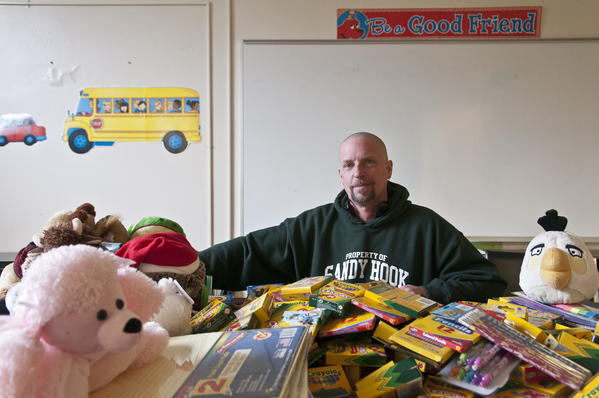 PATRICK CARROLL, a custodian at Buckley School, offered to shave his long hair for donations of coloring books and art supplies for children. He was affected by the Sandy Hook school shootings and, at left, delivered stuffed animals to memorials there.
