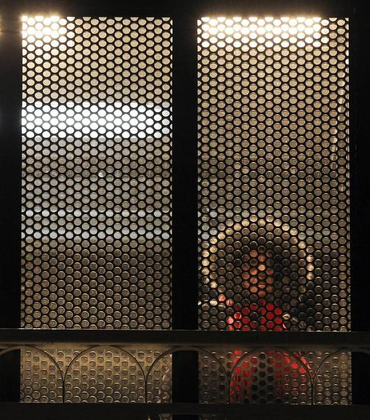 A CTA rider stand under a heat lamp shelter on the Damen Blue Line stop.