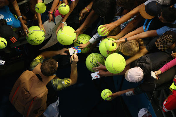 Andy Murray of Great Britain signs autographs after winning his fourth round match against Gilles Simon of France during day eight of the 2013 Australian Open at Melbourne Park on January 21, 2013 in Melbourne, Australia.