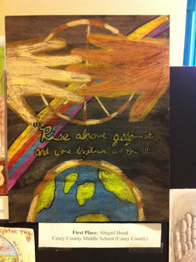 Abby Hood¿s award-winning painting includes an original quote by her, which reads, ¿Rising above judgment, coming together as one.¿