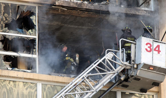 Firefighters work to extinguish a fire on the seventh and eighth floors of a high-rise apartment building in the 6700 block of South Shore Drive in Chicago.