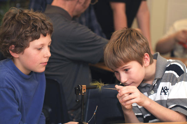 Grant Forbrig, (left) and Gavin Clear,  fifth-graders at Sheridan Elementary School, work together to carefully tie a fly. Several volunteers of the Miller-VanWinkle chapter of Trout Unlimited teach a fifth-grade class how to tie a fly for fly fishing recently during a gifted student class at Sheridan Elementary School in Petoskey.