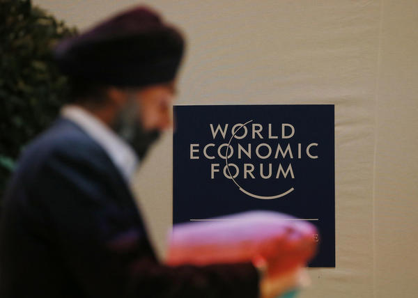 A man reads documents inside the Congress Hall of the World Economic Forum (WEF) at the Swiss Alpine resort of Davos January 22, 2013. The annual World Economic Forum is held from January 23 to 27, 2013 in Davos.