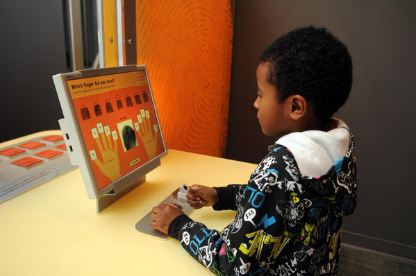 Malik Salaam, 7, of Cromwell examines his fingerprints at one of the activity stations at the science center's new exhibit.