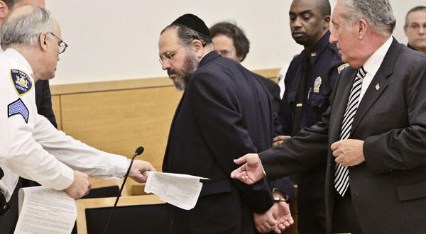 Nechemya Weberman, center, a religious counselor in a New York City ultra-Orthodox Jewish community, is lead away in handcuffs in Brooklyn Supreme Court.