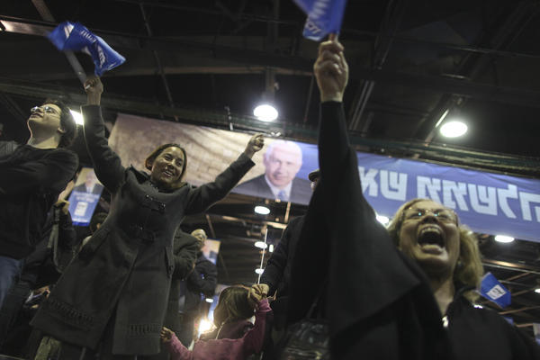 Supporters of Israeli Prime Minister Benjamin Netanyahu celebrate in Tel Aviv on Tuesday. His coalition appeared to have the edge over rivals in the day's election, according to exit polls.