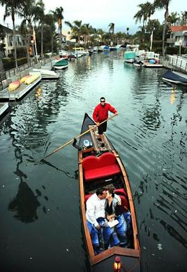 A couple kisses as they approach a bridge during a gondola ride through the Naples canal in Long Beach.