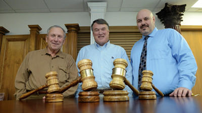 Somerset Door & Column President Dean Hottle, his son Bruce Hottle and SDC General Manager Bob McVicker pose behind gavels made from wood from the Shuster farm. On the left are gavels made of hickory hewn from an old barn beam and on the right are two carved from locust firewood cut on the property. The larger gavels are ceremonial and the smaller ones are those to be put to actual use.