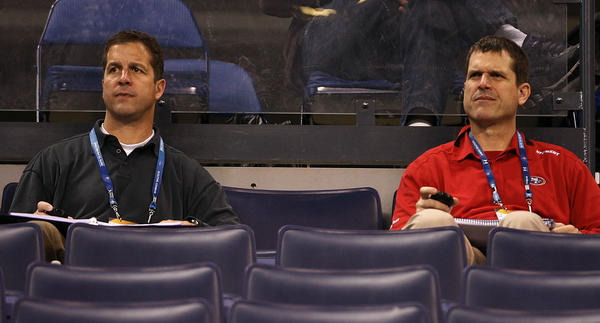 Baltimore Ravens coach John Harbaugh (left) and his brother San Francisco 49ers coach Jim Harbaugh watch the NFL scouting combine at Lucas Oil Stadium.