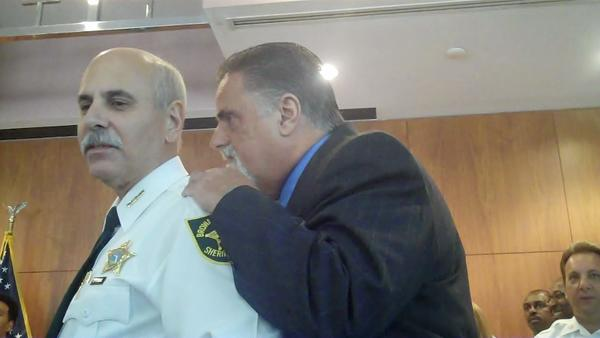 Art Santucci is one of the newcomers who got full payout of sick time and vacation leave. Here he is whispering to then-Sheriff Al Lamberti.