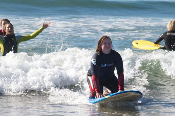 Liz Beautel of Irvine rides a wave during the Surf's Up For Down Syndrome event. Courtney Conlogue, left, cheers her on.