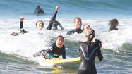Jeremy Fraser of Tustin smiles has he rides a wave during the Surf's Up For Down Syndrome event.