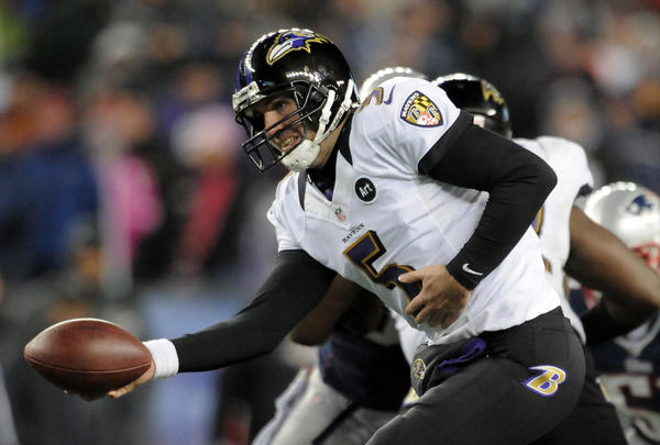 Ravens quarterback Joe Flacco hands off the ball against the New England Patriots.