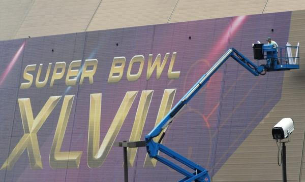 Workers place a sign on the Superdome in New Orleans, where the game takes place Feb. 3.