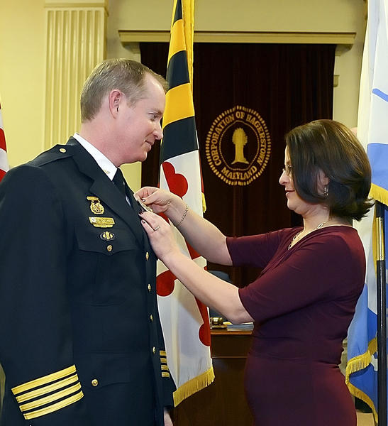Hagerstown City Police Chief Mark Holtzman has his badge pinned on by his wife, Laura Holtzman, after being sworn in Tuesday evening in the city council chambers.