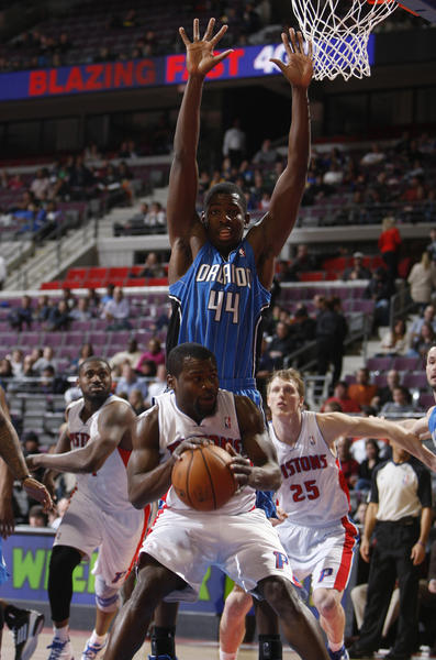 The Detroit Pistons' Will Bynum drives against the Orlando Magic's Andrew Nicholson, top, during second-period action at The Palace of Auburn Hill