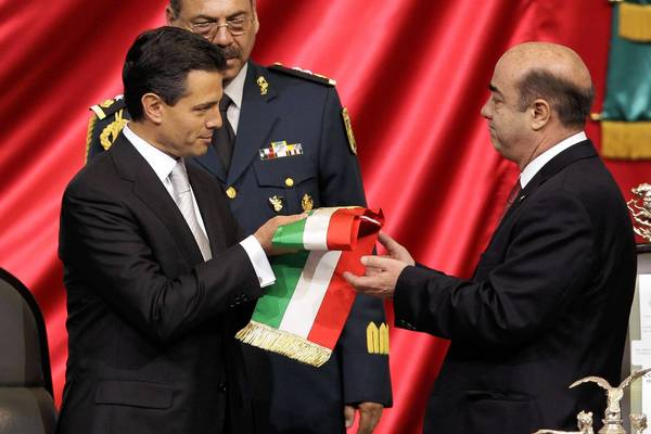 Enrique Pena Nieto, left, receives the presidential sash from Jesus Murillo Karam, president of the lower house, during the presidential inauguration ceremony Dec. 1 in Mexico City. Murillo Karam is now Mexico's attorney general.