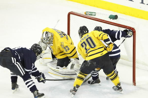 Quinnipiac Bobcats goaltender Eric Hartzell (33) makes the save against Connecticut Huskies forward Sean Ambrosie (21) and forward Jordan Sims (19)during the third period at the TD Bank Sports Center. Quinnipiac defeated UConn 2-1.