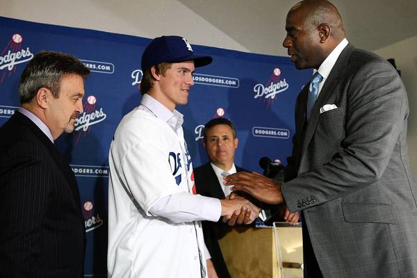 The Dodgers' new TV deal would help cover its recent spending spree, including a six-year, $147-million contract with pitcher Zack Greinke, shown with General Manager Ned Colletti, left, and owner Magic Johnson.