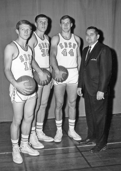 Jim Marking with South Dakota State players and brothers Gary Thomas (12), John Thomas (30) and Mel Thomas (44).