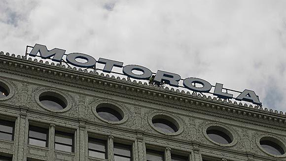 Workers finish putting a Motorola sign where the Santa Fe sign once stood atop the building at 224 S. Michigan Ave. in July.
