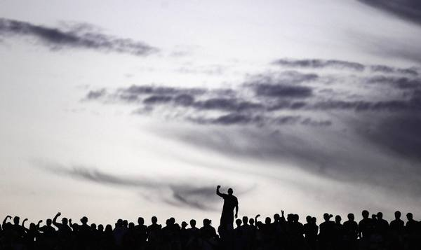 Supporters of Argentina's Tigre are silhouetted as they cheer during their Copa Libertadores soccer match against Venezuela's Deportivo Anzoategui in Buenos Aires January 22, 2013.