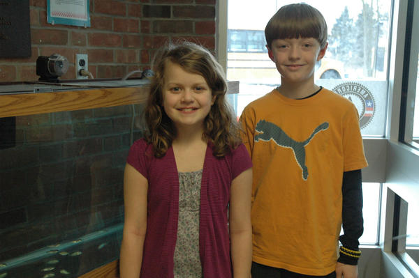Sheridan elementary fifth graders Kaitlyn Smith and Sean Redman, both 10, stand next to the tank that holds salmon the students have raised from eggs.