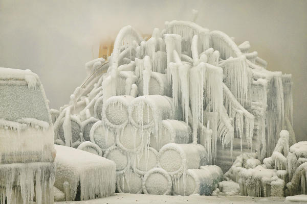 A truck and chemical drums are covered with ice as firefighters help to extinguish a massive blaze at a vacant warehouse on January 23, 2013 in Chicago, Illinois. More than 200 firefighters battled a five-alarm fire as temperatures were in the single digits.
